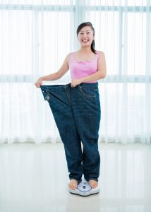 Young woman standing on a measuring scale and showing her success after losing weight.