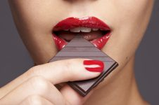 Closeup portrait of a cute young female biting into a piece of chocolate